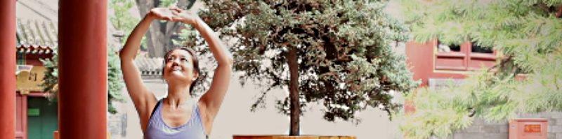 smiling Mimi Kuo-Deemer demonstrates Qi Gong pose